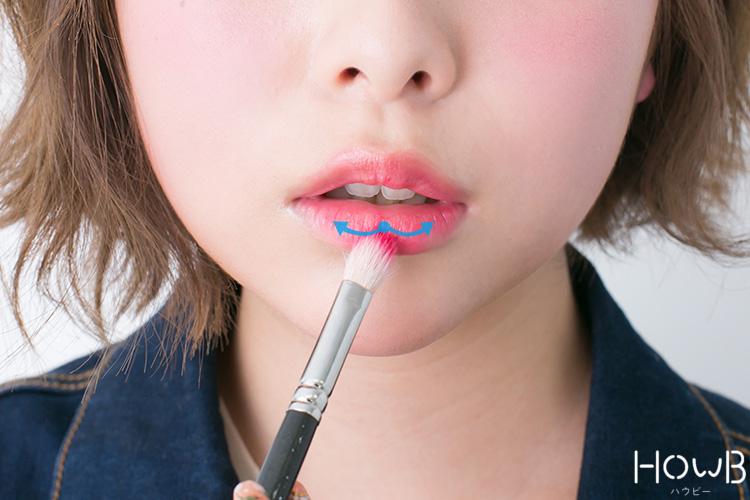 リップメイクのプロセス ブラシでグロスを下唇に塗る 口元アップ
