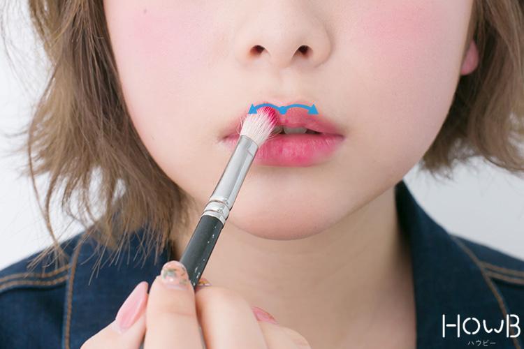 リップメイクのプロセス ブラシでグロスを上唇に塗る 口元アップ