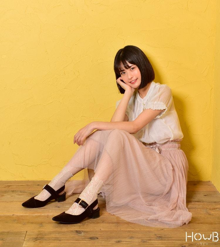横田ひかる全身 白トップスとピンクのスカート 座っている