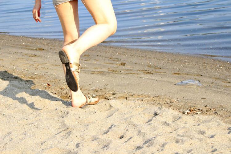 ビーチを走る女性の足