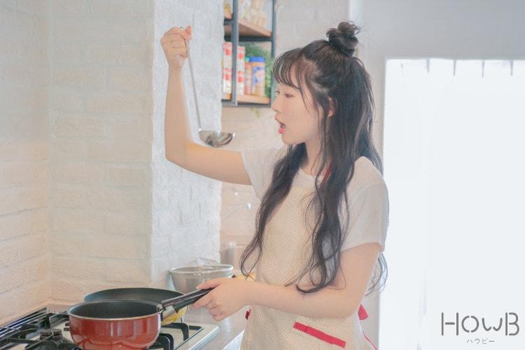 片手鍋とお玉を持つ料理中の越智ゆらのちゃん