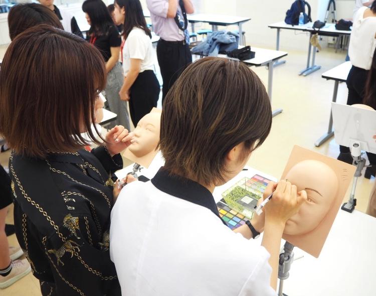 シリコン製の顔にメイクをするおとっぴーと志賀さん