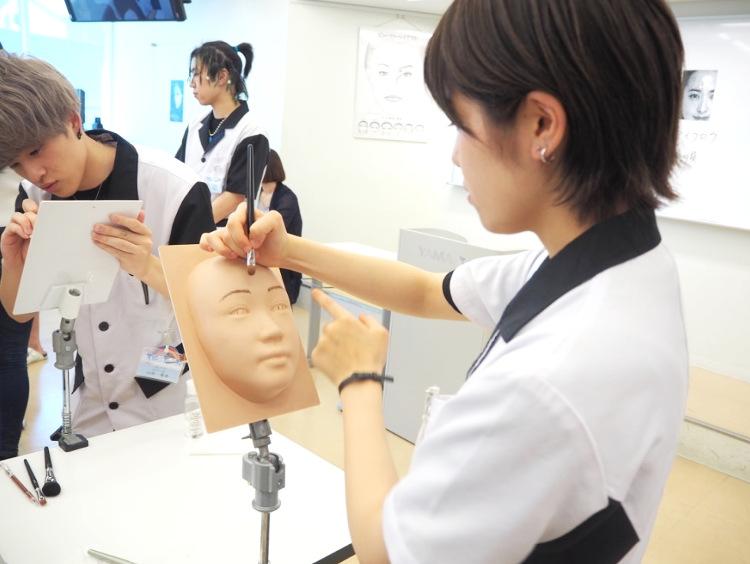 シリコン製の顔にメイクをする志賀さん